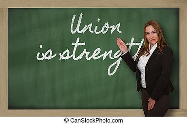 Teacher showing Union is strength on blackboard -...