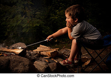 Boy cooking marshmallow - Little boy cooking a marshmallow...