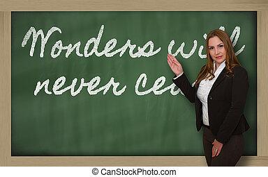 Teacher showing Wonders will never cease on blackboard -...