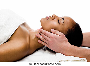 facial massage - young woman receiving facial massage with...