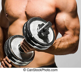 man working out with dumbbells - Handsome muscular man...