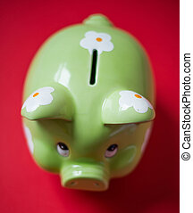Green piggy bank on a red background