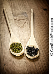 Soybeans and black beans in wooden spoons - Green soybeans...