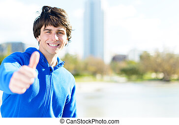 Portrait Of Young Man Showing Thumb-up Sign