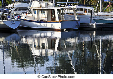 Moored sailboats reflecting in water - Moored sailboats...