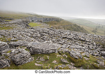 Fog sweeps over limestone pavement at Malham Cove in Yorkshire Dales National Park