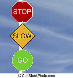 Stop Slow Go road signs against a blue sky background
