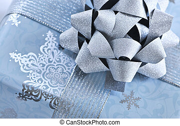 Christmas gift box wrapped in blue paper with silver ribbon...