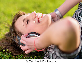 Young Woman Listening To Music - Woman Lying On Grass With...