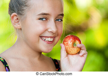 Face shot of cute girl holding red apple.