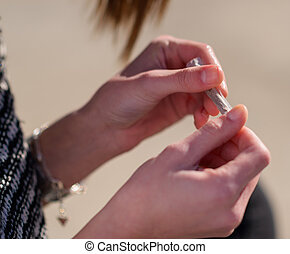 Closeup Of Womans Hand Rolling Cigarette, Outdoors