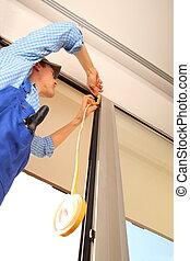 Handwerker dichtet Fensterrahmen ab