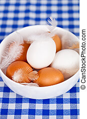 brown and white eggs, feathers in a bowl on tablecloth...