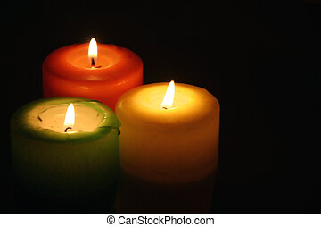 three colorful candles side