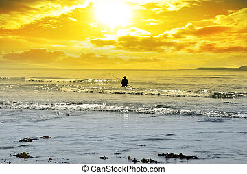 man fishing among the waves of the Atlantic ocean in...