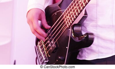 Playing the bass guitar - Man playing electric bass guitar
