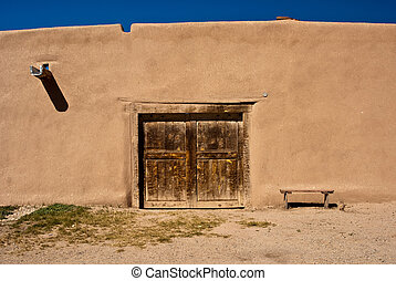 Adobe building with old door and bench in New Mexico, USA