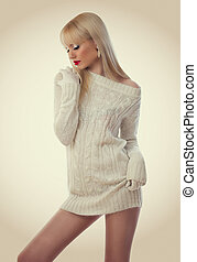 Beautiful blonde young woman in knitted dress