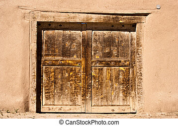Old door in adobe wall - Old door and adobe wall in New...