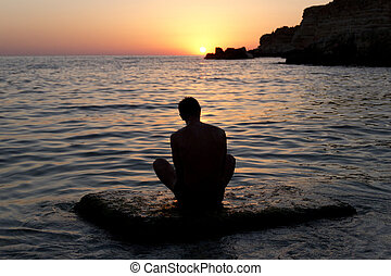 Man meditating at sunset - The man meditating by the sea at...