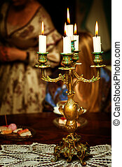 Retro golden candlestick with five candles with flame