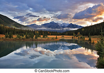 The cold lake, forest and snow mountains in Canada - Dark...