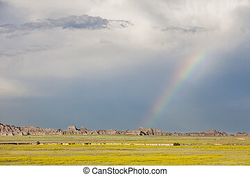 Rainbow and storm clouds over Badlands National Park, South...