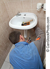 Plumber fixing water tap in a bathroom