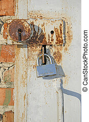 Two old locks - An old ferruginous metallic door is closed...