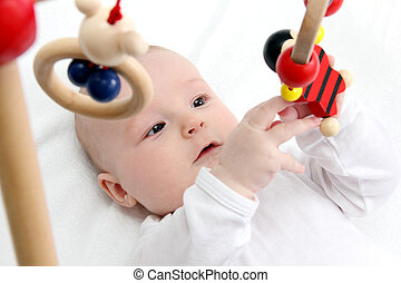 Baby with toys - Beautiful baby on back playing with toys