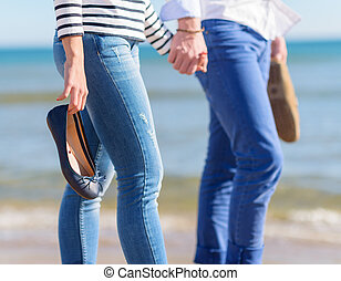 Couple Walking Together On Beach - Young Couple Holding...
