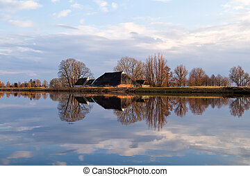 Dutch farmhouse by river before sunset