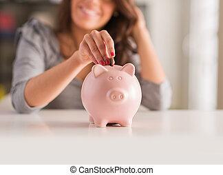 mujer, poniendo, moneda, en, cerdito, Banco