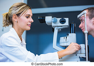 Optometry concept - handsome young man having his eyes...