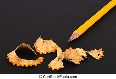 Sharpened pencil and wooden shavings on dark background.