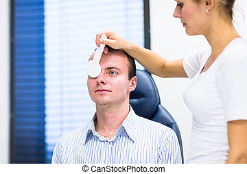 Optometry concept - handsome young man having his eyes examined by an eye doctor