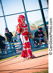 Little league baseball catcher standing up at home plate...