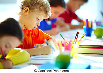 Schoolboy at lesson - Portrait of cute schoolboy drawing at...