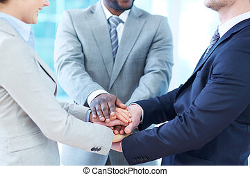 Partnership - Close-up of business partners making pile of...
