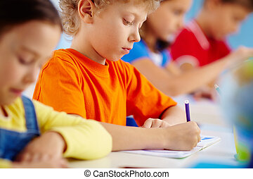 Serious pupil - Shot of a serious pupil writing in his...