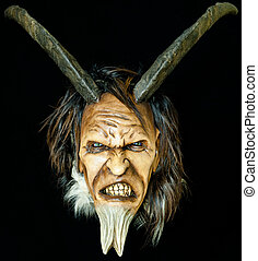 wooden satan evil mask with horns and fur beard on black