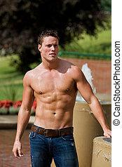 Athletic male model - A fit male model outside beside a...
