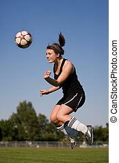 Woman soccer player - A female soccer player heading the...