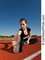 Stretch - A beautiful woman stretching before a race at the...