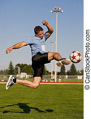Soccer kick - Athletic male in the air kicking a soccer ball