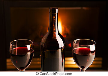 Wine and fireplace - A bottle of red wine and two glasses in...