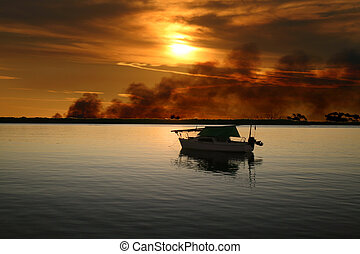 Yacht With Wild Fire - Sailing boat moored with a wild fire...
