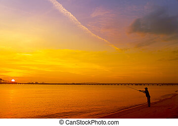 man fishing silhouette near commercial jetty