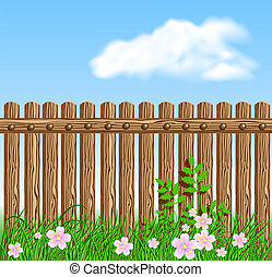 Wooden fence on green grass with flowers against the sky