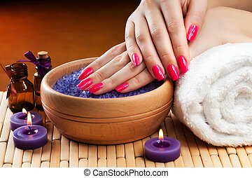 female hands with aromatic candles and towel. Spa - lavender...